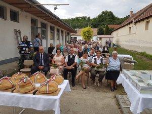 A közönség, a nemzeti szalaggal átkötött új kenyér és jobb oldalon Király Kata könyve a kesztölci népdalokról